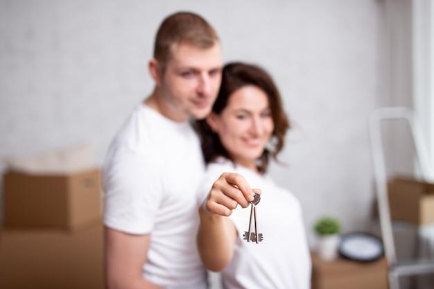 Jour de déménagement - jeune couple tenant les clés de leur nouvelle maison ou appartement. se concentrer sur les clés