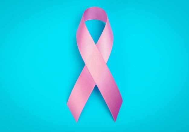 Jour du cancer du monde: breast cancer awareness ribbon sur bleu backgr