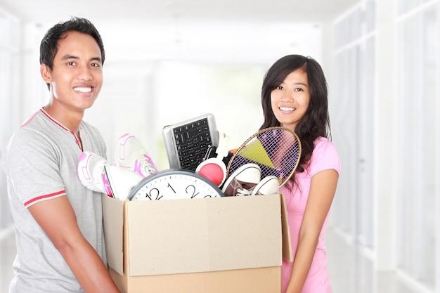 Jour du déménagement. couple avec leurs affaires à l'intérieur de la boîte en carton