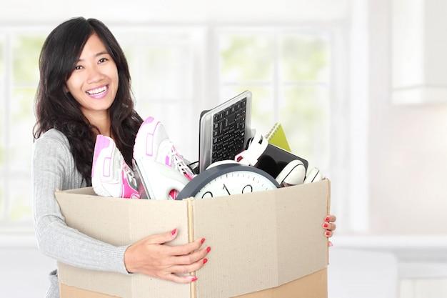 Jour du déménagement. femme avec ses affaires à l'intérieur de la boîte en carton
