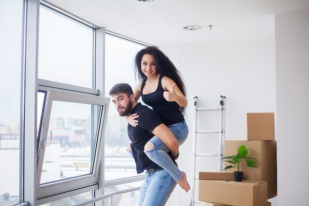 Jour du déménagement. heureux jeune couple transportant des boîtes