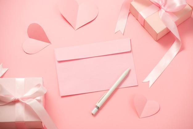 Le jour de la femme; modèle romantique; maquette avec du papier coeur; cadeau boîte rose; ruban d'arc et enveloppe en fond rose
