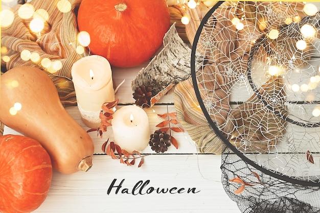 Jour d'halloween citrouilles mûres à côté de guirlandes lumineuses feuilles d'automne bougies magiques et chapeau de sorcière