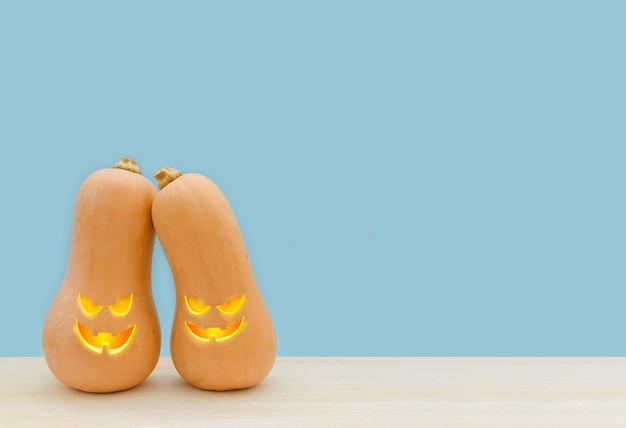 Jour d'halloween deux citrouilles mignonnes avec des grimaces se tiennent sur un fond bleu
