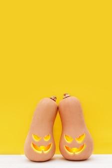 Jour d'halloween deux citrouilles mignonnes avec des grimaces se tiennent sur fond jaune fête de vacances