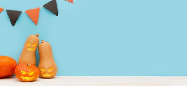 Jour d'halloween trois citrouilles mignonnes avec des grimaces se tiennent à côté de drapeaux colorés