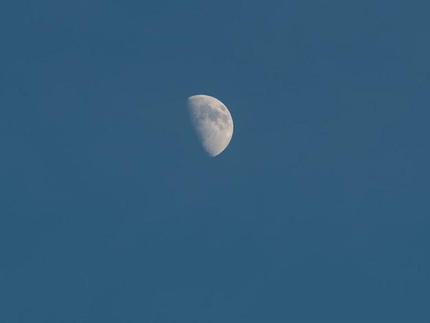 Jour de la lune dans le ciel bleu