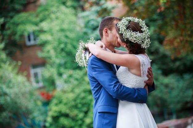 Jour de mariage. heureux jeunes mariés. moment romantique de mariage. mariée et le marié s'embrasser à l'extérieur