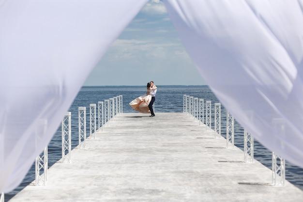 . jour de mariage. homme portant sa petite amie dans les bras marchant sur le pont. portrait de gens heureux amoureux. moment romantique à la date