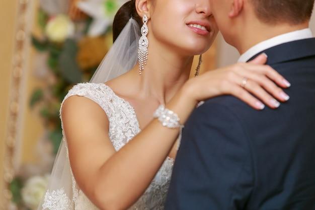 Jour de mariage. jeunes mariés s'embrassant pendant la cérémonie de mariage. étreintes passionnées d'un couple d'amoureux. marié avec boutonnière étreignant doucement la mariée avec un bouquet rouge de mariage. moment romantique de mariage. tout juste marié
