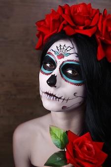 Le jour des morts. halloween. jeune femme au jour du crâne masque mort face à l'art et a augmenté. fond sombre.