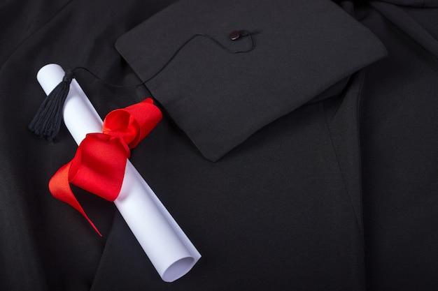Jour de l'obtention du diplôme. une blouse, une casquette de graduation et un diplôme et disposés pour le jour de la remise des diplômes