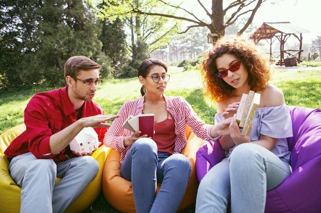 Jour ouvrable. bel homme déterminé assis en plein air avec ses collègues et discutant de leur projet