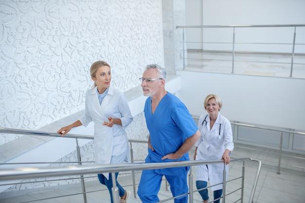 Jour ouvrable. groupe de travailleurs médicaux professionnels à l'étage, ayant une conversation amicale