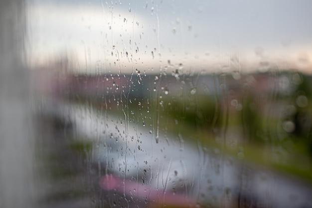 Jour de pluie à travers la fenêtre sur fond de ciel et de bâtiments de la ville