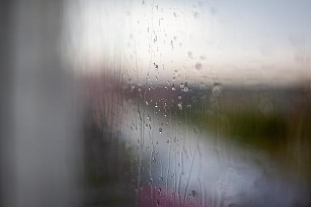 Jour de pluie à travers la fenêtre sur fond de ciel gris nuageux et bâtiments de la ville. concept. paysage urbain du soir derrière la vitre avec des gouttes d'eau qui coulent.