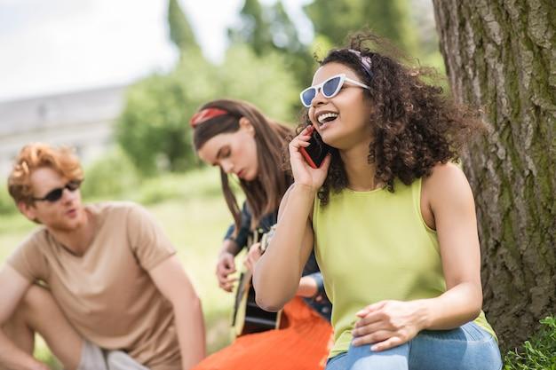 Jour de repos, repos. joyeuse jeune fille aux cheveux bouclés parlant sur smartphone et amis avec guitare assis derrière un arbre au pique-nique