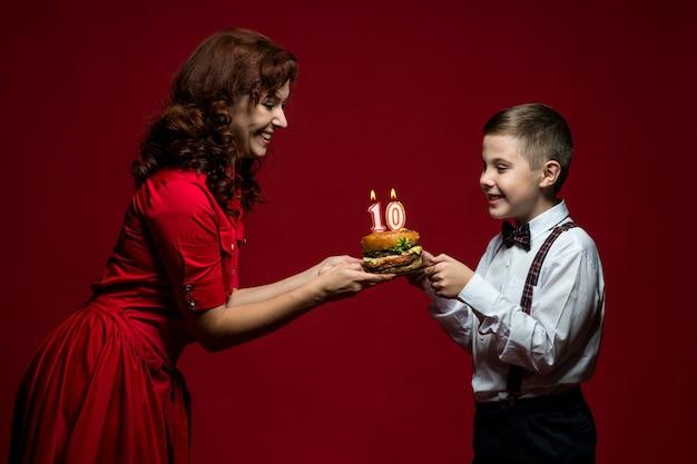 Jour de restauration rapide, jour de hamburger, jour de hamburger. close-up portrait de maman et fils avec restauration rapide dans leurs mains