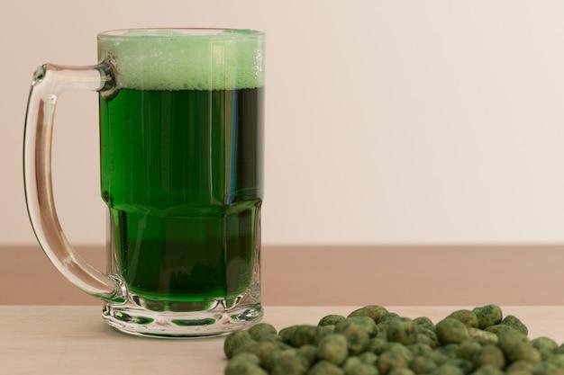 Le jour de la saint-patrick. verre de bière verte et cacahuètes vertes