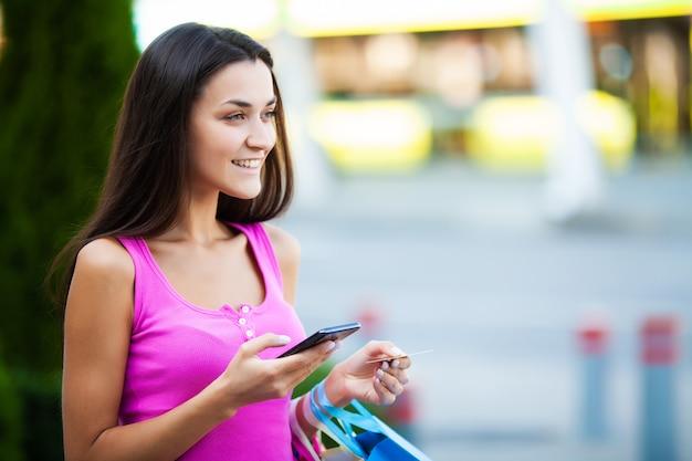 Jour de shopping. femme tenant des sacs colorés près de son centre commercial shooping en vacances vendredi noir.