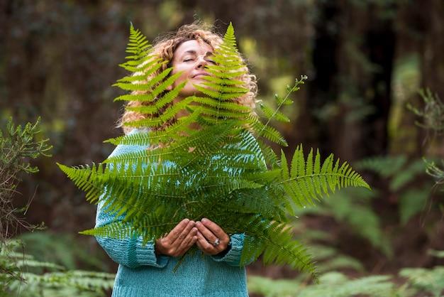 Jour de la terre et concept d'amour pour la nature avec une belle femme aux yeux fermés, ressentez la grande feuille et profitez de l'activité de loisirs naturels en plein air - sauvez la forêt et pas de mode de vie de déforestation