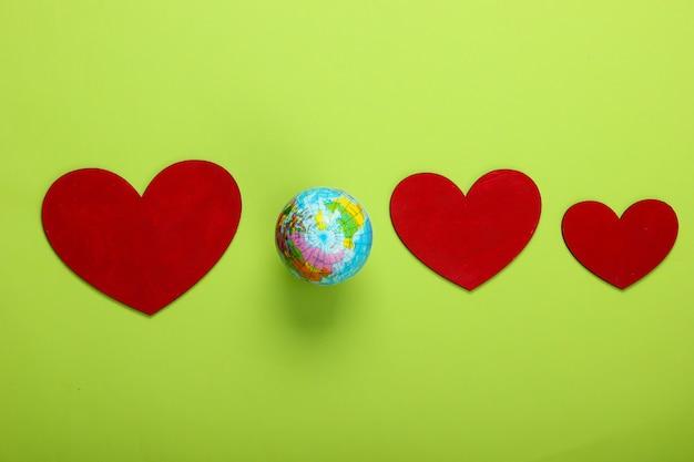 Jour de la terre. globe avec des coeurs sur un vert.