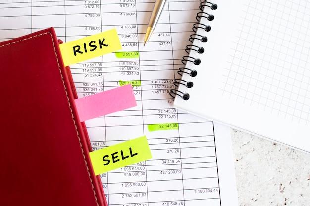 Un journal d'affaires avec des onglets colorés avec des inscriptions se trouve sur des graphiques financiers sur le bureau.