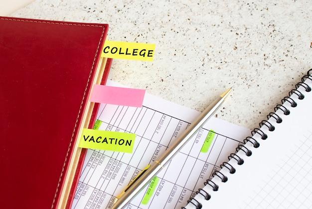 Un journal d'affaires avec des onglets colorés avec des inscriptions se trouve sur les graphiques financiers sur le bureau.