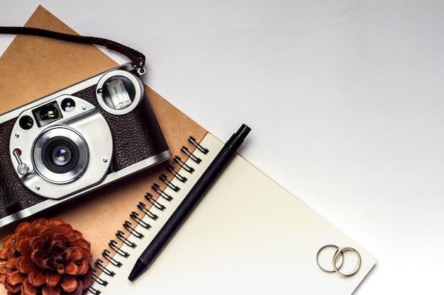 Journal avec appareil photo, bagues, pomme de pin et crayon
