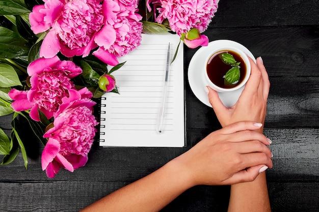 Journal d'écriture de main de femme avec du café.