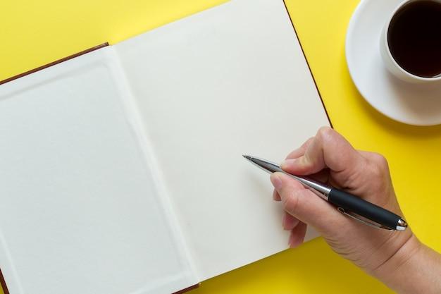 Journal ouvert, stylo écrit à la main et tasse de café