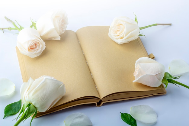 Journal ouvert vierge avec des roses blanches