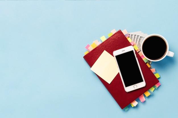 Journal rouge avec des autocollants sur les pages, une tasse de café noir, cent dollars, téléphone blanc, fond bleu. concept d'entreprise réussie, bonne planification, gestion du temps. mise à plat, vue de dessus