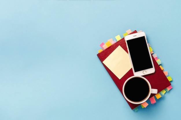 Journal rouge avec des autocollants sur les pages, une tasse de café noir, téléphone blanc, fond bleu. concept d'entreprise réussie, bonne planification, gestion du temps. mise à plat, vue de dessus