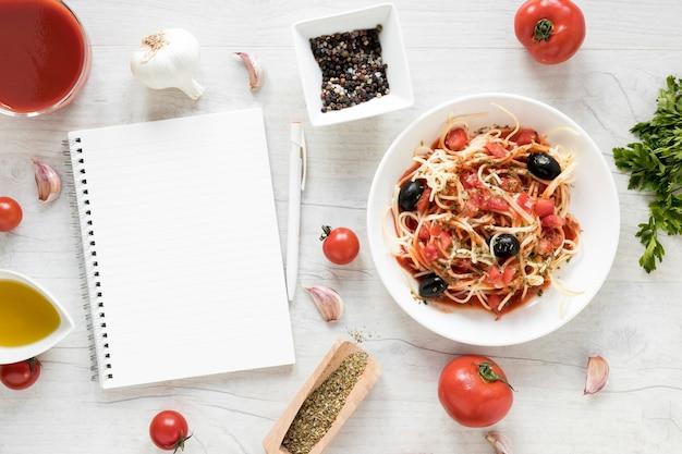 Journal vierge et de délicieuses pâtes spaghettis avec des ingrédients frais sur une table en bois blanche