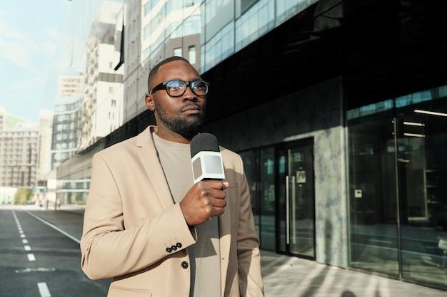 Journaliste africain tenant un microphone et parlant, il travaille dans la chaîne d'information