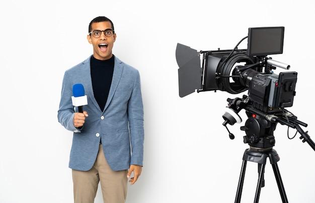 Journaliste afro-américain tenant un microphone et rapportant des nouvelles sur un mur blanc isolé avec une expression faciale surprise