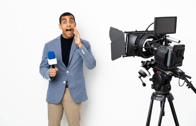 Journaliste afro-américain tenant un microphone et rapportant des nouvelles sur un mur blanc isolé avec surprise et expression faciale choquée