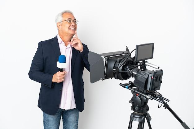 Journaliste d'âge moyen brésilien homme tenant un microphone et rapport de nouvelles isolé sur fond blanc en pensant à une idée tout en regardant
