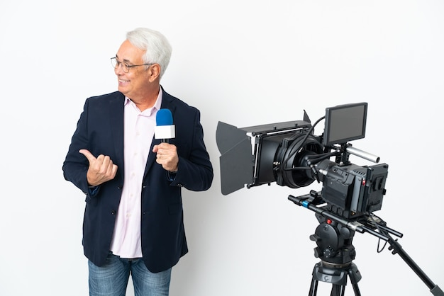 Journaliste d'âge moyen brésilien homme tenant un microphone et rapport de nouvelles isolé sur fond blanc pointant vers le côté pour présenter un produit