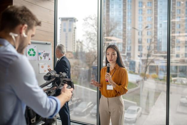 Une journaliste aux cheveux noirs a l'air confiante tout en parlant à la caméra vidéo
