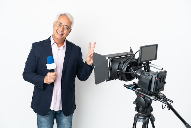 Journaliste brésilien d'âge moyen tenant un microphone et rapportant des nouvelles isolées sur fond blanc souriant et montrant le signe de la victoire