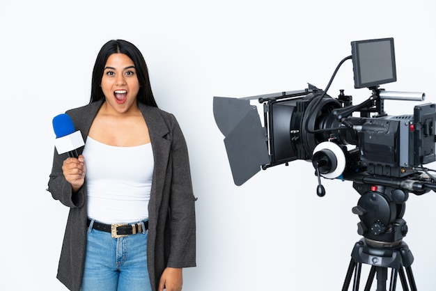 Journaliste colombienne femme tenant un microphone et rapportant des nouvelles sur le mur blanc avec une expression faciale surprise