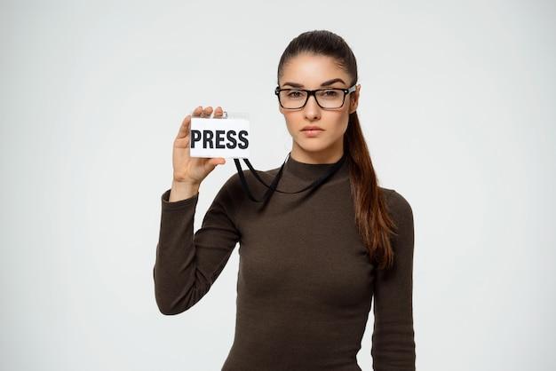 Journaliste femme sérieuse montrant l'insigne de presse