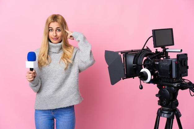 Journaliste femme tenant un microphone et rapportant des nouvelles sur l'espace rose isolé ayant des doutes et de la pensée