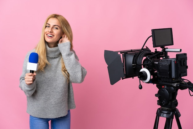 Journaliste femme tenant un microphone et rapportant des nouvelles sur un espace rose isolé en écoutant quelque chose en mettant la main sur l'oreille