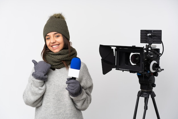 Journaliste femme tenant un microphone et rapportant des nouvelles avec le geste du pouce levé et souriant