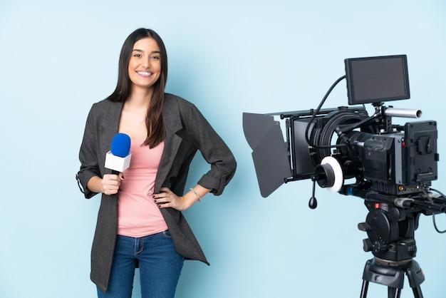 Journaliste femme tenant un microphone et rapportant des nouvelles isolé sur bleu
