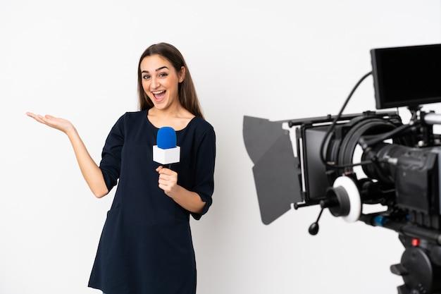 Journaliste femme tenant un microphone et rapportant des nouvelles isolé sur mur blanc avec une expression faciale choquée