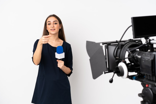 Journaliste femme tenant un microphone et rapportant des nouvelles isolé sur mur blanc surpris et pointant vers l'avant